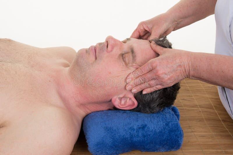 Massaggiatore che fa massaggio capo delle tempie sull'uomo fotografia stock libera da diritti
