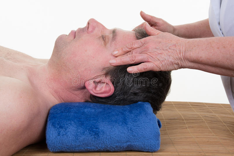 Massaggiatore che fa massaggio capo delle tempie sull'uomo fotografia stock