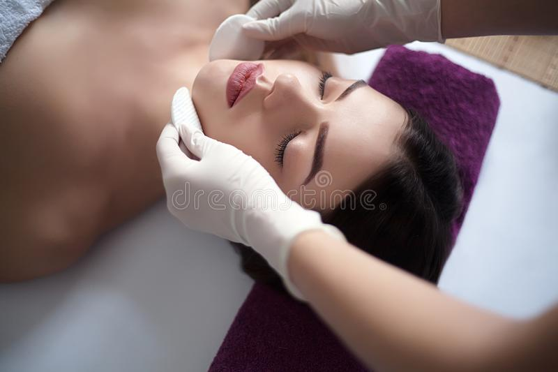 Massaggiatore che fa massaggio la testa di una donna adulta nel salone della stazione termale fotografie stock