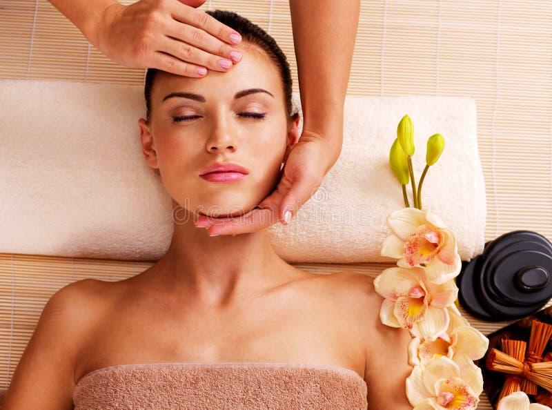 Massaggiatore che fa massaggio la testa di una donna nel salone della stazione termale immagine stock