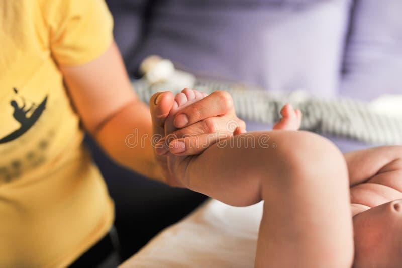 Massaggiatore che fa massaggio per il piccolo bambino del piede fotografia stock libera da diritti