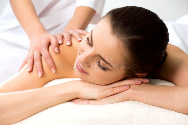 Massaggiatore che fa massaggio sul retro della donna nel salone della stazione termale immagini stock libere da diritti