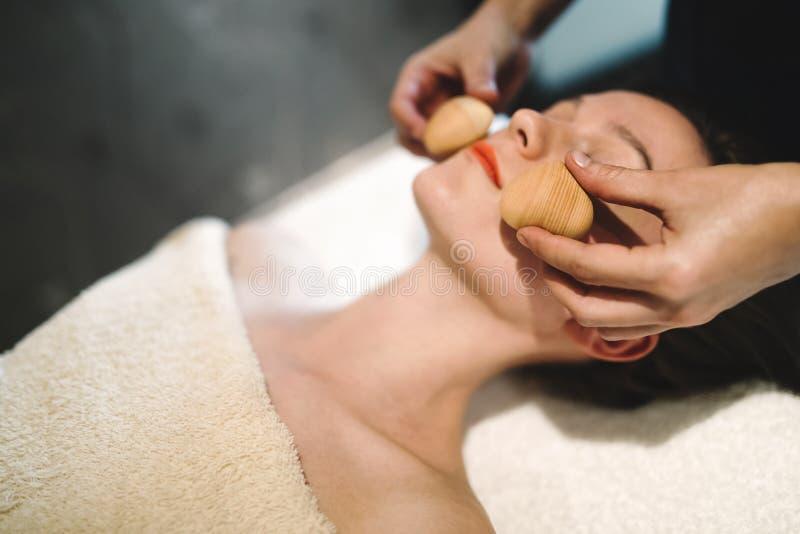 Massaggiatore che massaggia fronte con gli oggetti riscaldati fotografia stock libera da diritti
