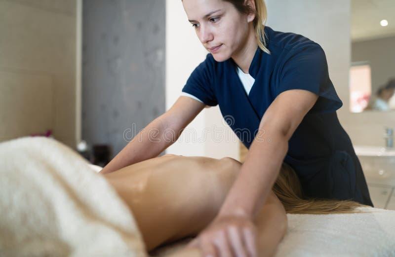 Massaggiatore che massaggia indietro della femmina fotografia stock