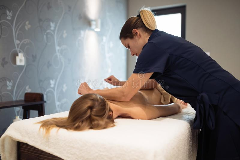 Massaggiatore che massaggia indietro della femmina fotografie stock libere da diritti