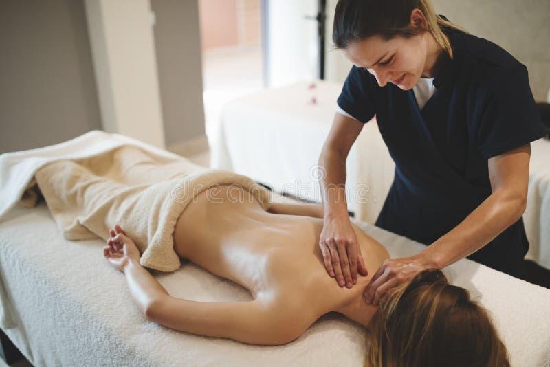 Massaggiatore che massaggia indietro della femmina fotografia stock libera da diritti