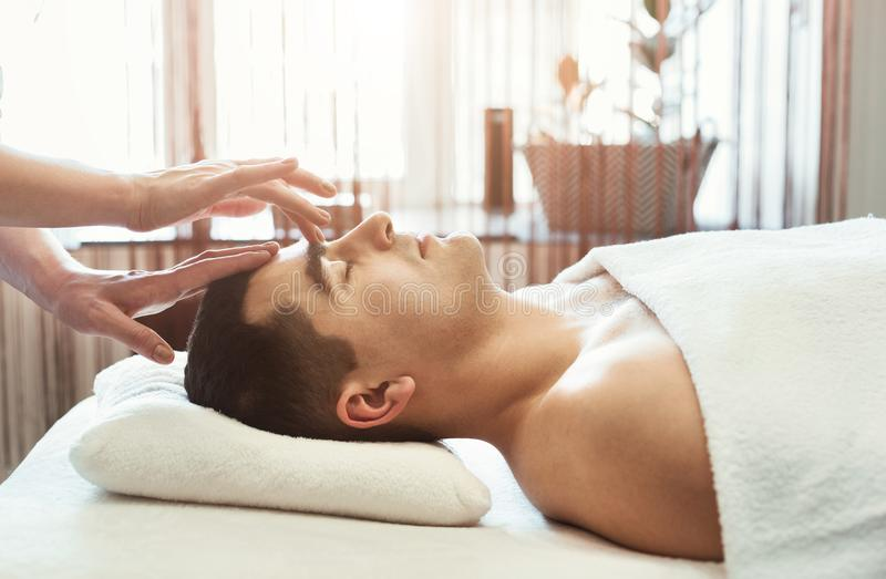 Massaggiatore femminile che fa massaggio capo all'uomo fotografia stock libera da diritti