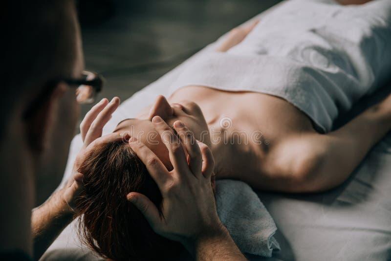 Massaggiatore maschio che fa massaggio di fronte ringiovanente e di rilassamento alla donna fotografie stock