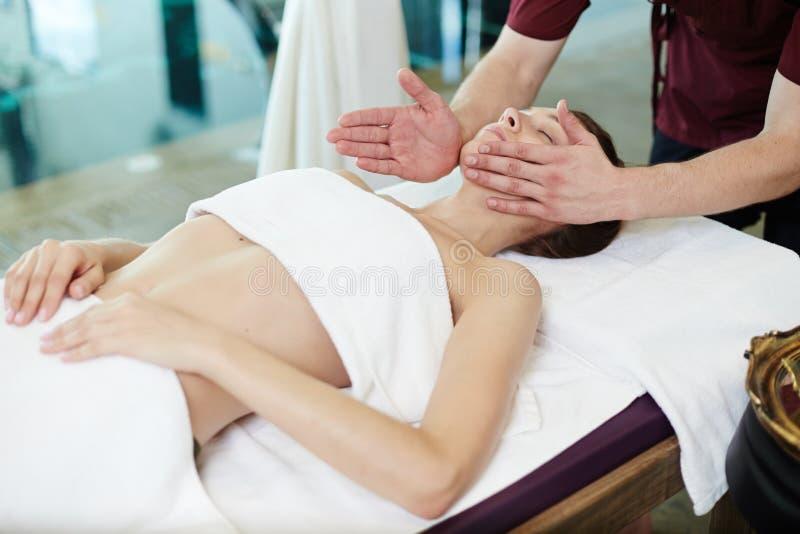 Massaggiatore maschio che massaggia giovane donna in STAZIONE TERMALE immagini stock
