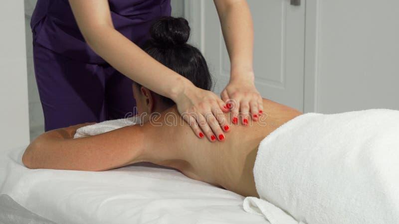 Massaggiatrice professionista che massaggiano indietro e spalle di un cliente fotografia stock libera da diritti