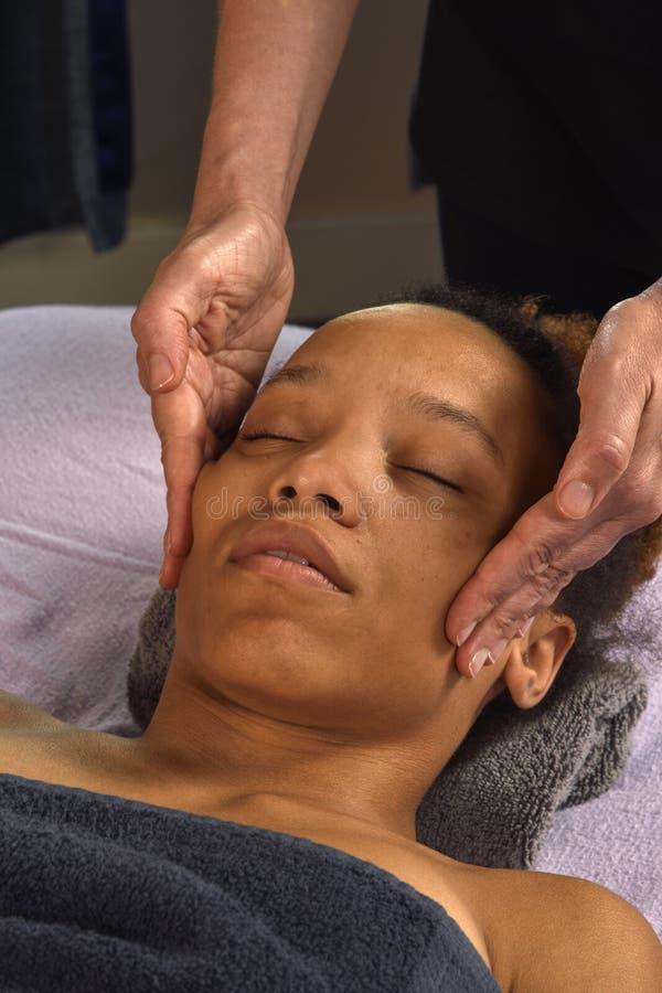 Massaggio del fronte della giovane donna alla stazione termale di giorno immagine stock
