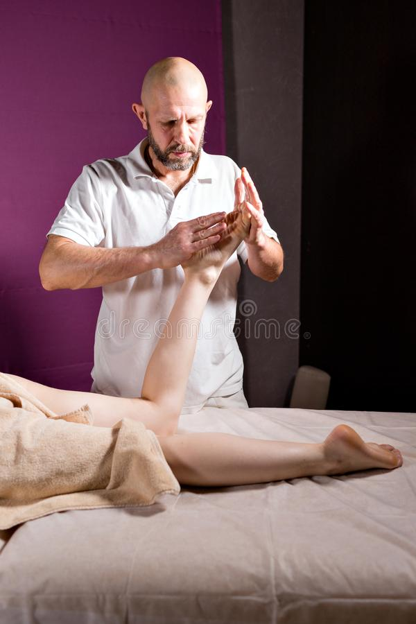 Massaggio del piede di benessere Chiuda su dell'osteologo che fa il massaggio manipolatore Mani dell'uomo che massaggiano femmina fotografia stock