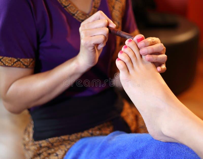 Massaggio del piede di reflessologia, trattamento del piede della stazione termale dal bastone di legno fotografia stock