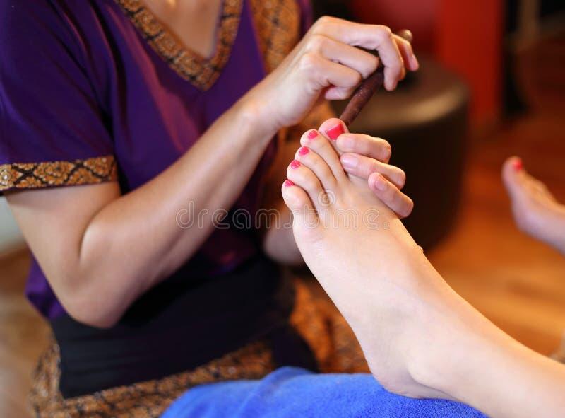 Massaggio del piede di reflessologia, trattamento del piede della stazione termale dal bastone di legno fotografia stock libera da diritti