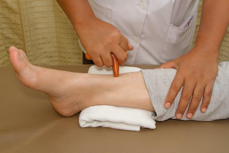 Massaggio del piede di reflessologia, trattamento del piede della stazione termale dal bastone di legno fotografie stock