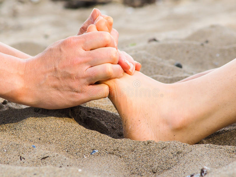 Massaggio del piede in sabbia, in maschio ed in caucasian femminile fotografia stock libera da diritti