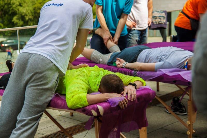 Massaggio di sport Terapista di massaggio che massaggia le spalle e le gambe degli atleti, funzionanti con il muscolo trapezio immagine stock