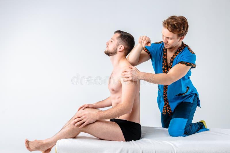 Massaggio di tema e cura del corpo Un medico maschio caucasico bello nell'uniforme e nella barba del blu che diagnostica i muscol fotografia stock libera da diritti