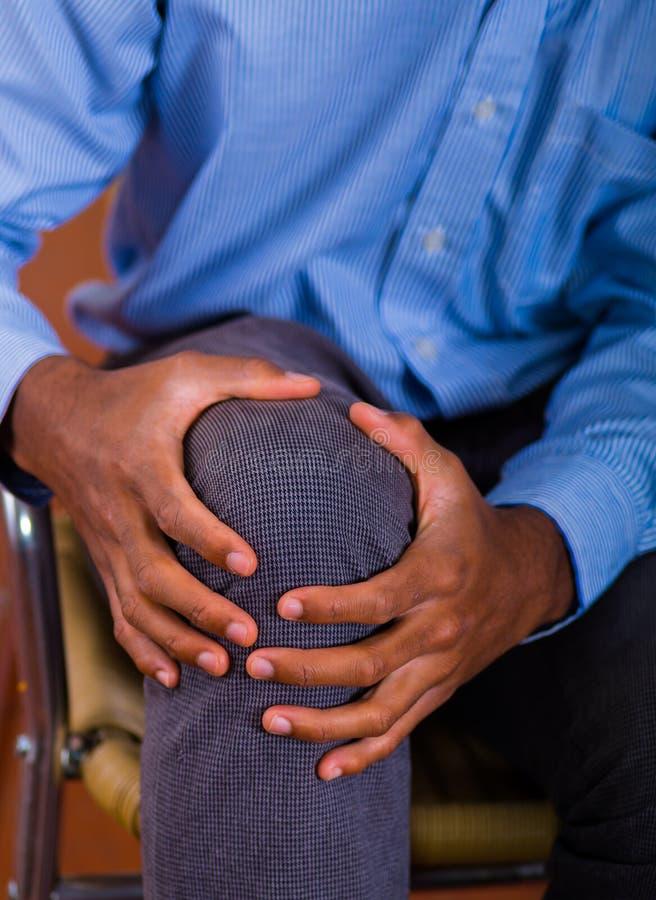 Massaggio quando il dolore viene, aiuto del ginocchio di entrambe le mani fotografia stock libera da diritti