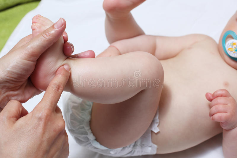Massaging child's foot stock images