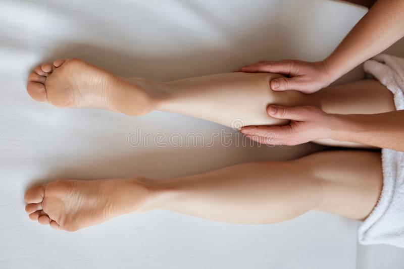 Massaging tired muscles. Close-up of massage therapist massaging beautiful female leg. stock image
