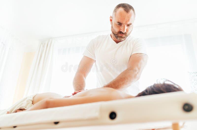 Massagista farpado que faz para trás uma massagem terapêutica para uma menina que encontra-se em um sofá da massagem em uns terma imagens de stock