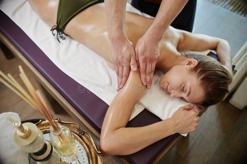Massagista masculino Massaging Young Woman nos TERMAS foto de stock royalty free