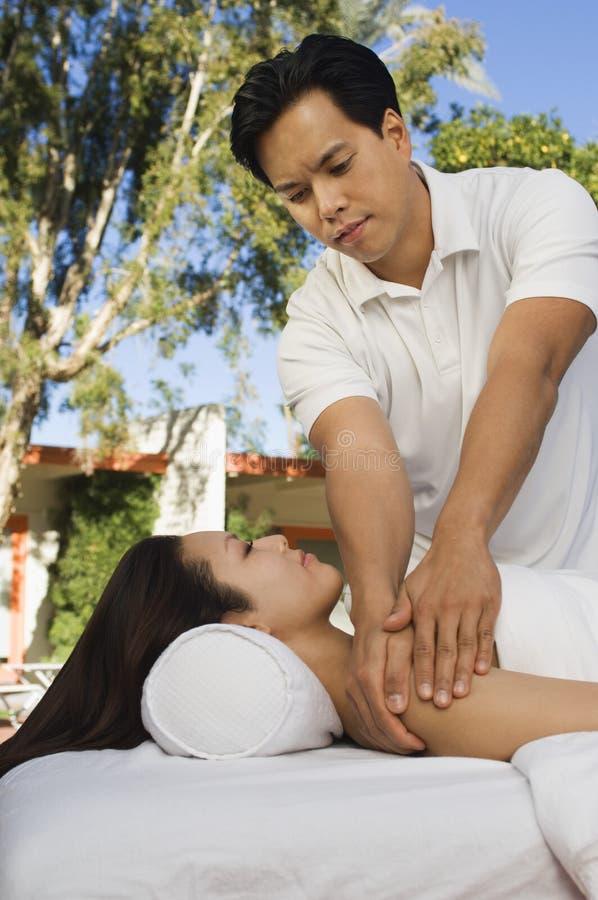 Massagista Massaging Young Woman imagens de stock royalty free