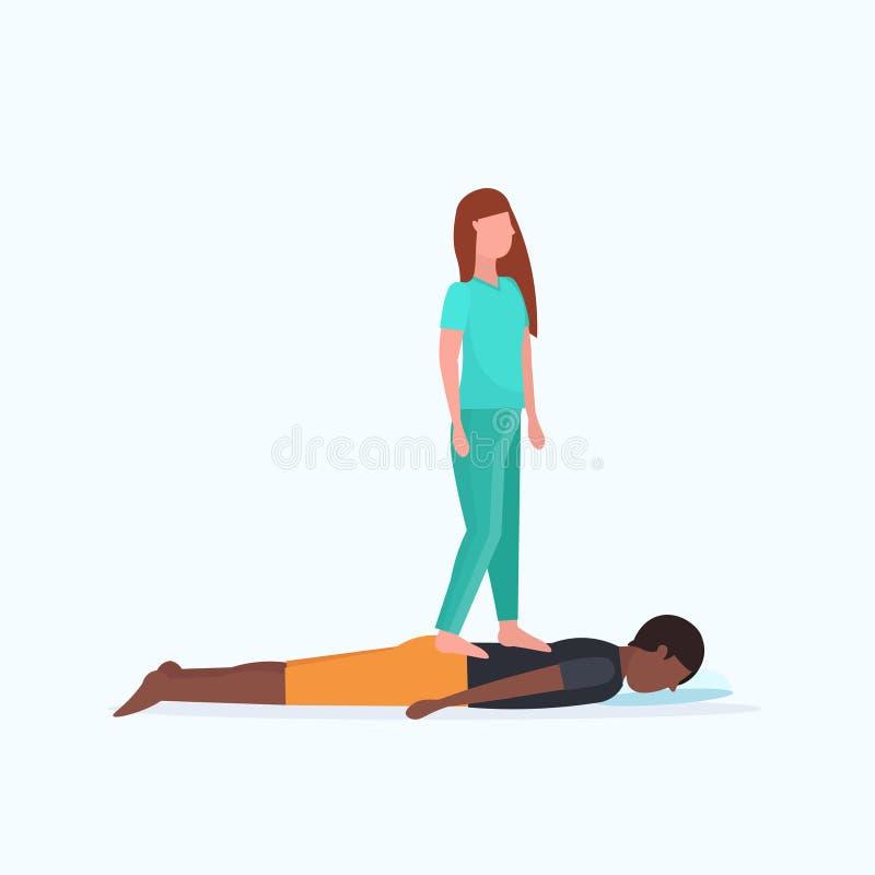 Massagista na posição uniforme no paciente que faz para trás o indivíduo afro-americano do tratamento cura que tem o manual da ma ilustração stock