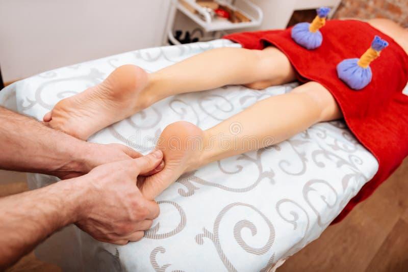 Massagista profissional no salão de beleza dos TERMAS que pressiona em pontos especiais nos pés imagens de stock royalty free