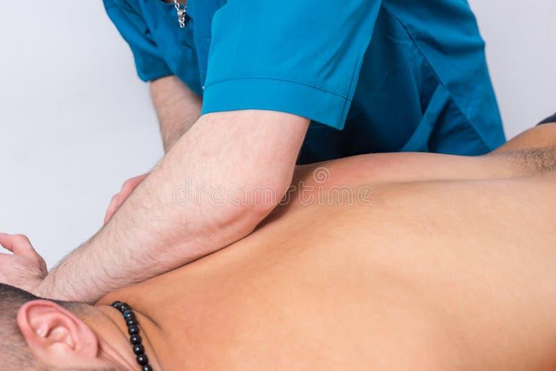Massagista profissional que executa uma massagem espinal imagem de stock royalty free