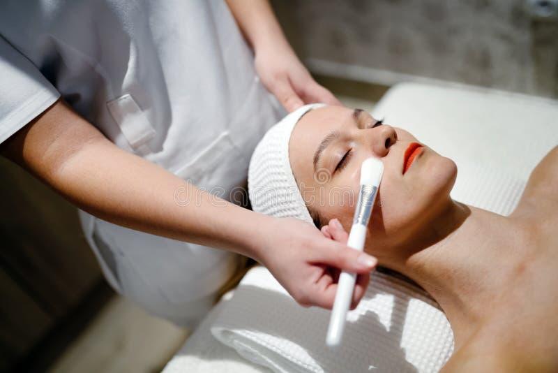 Massagista que aplica a máscara protetora imagem de stock