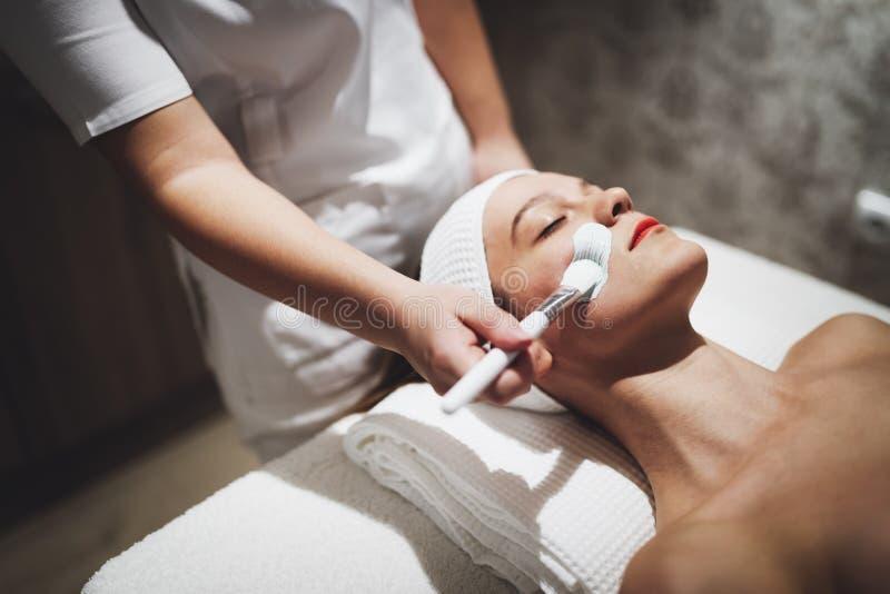 Massagista que aplica a máscara protetora foto de stock