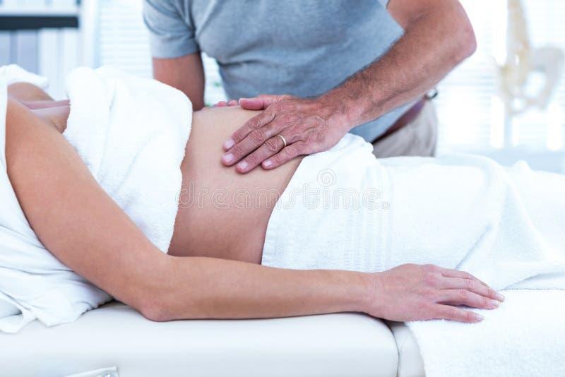 Massagista que dá a massagem à mulher gravida foto de stock royalty free