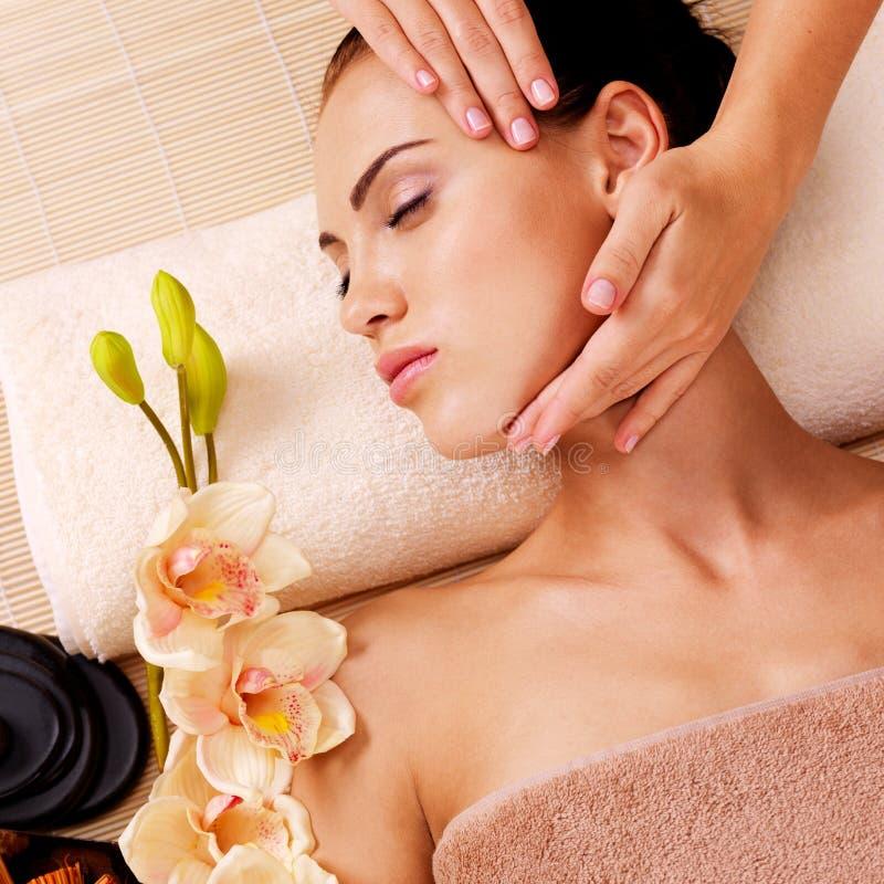 Massagista que faz a massagem a cabeça de uma mulher no salão de beleza dos termas foto de stock