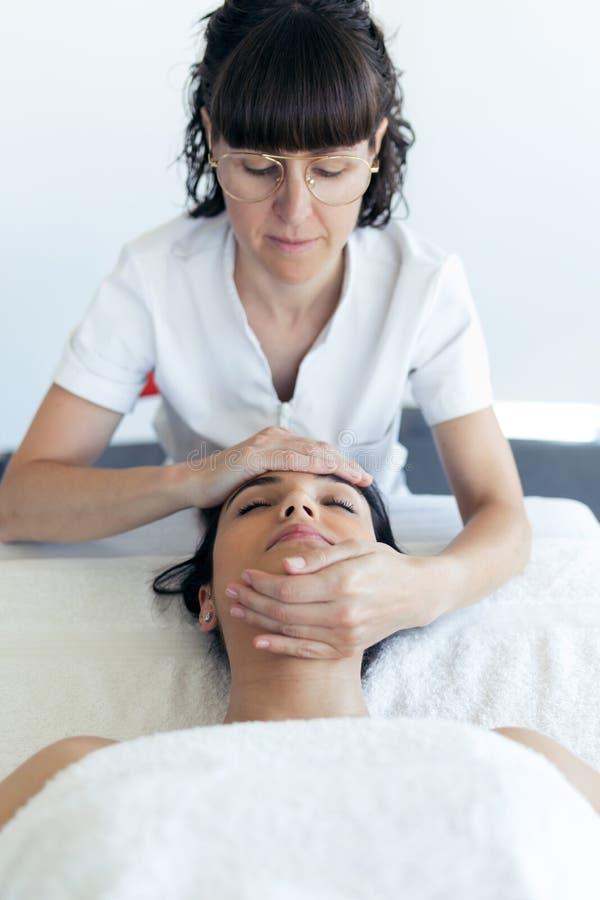 Massagista que faz a massagem de cara terapêutica à mulher gravida nova no centro dos termas fotos de stock