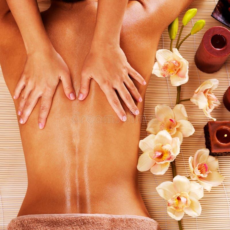 Massagista que faz a massagem na parte traseira da mulher no salão de beleza dos termas imagens de stock royalty free