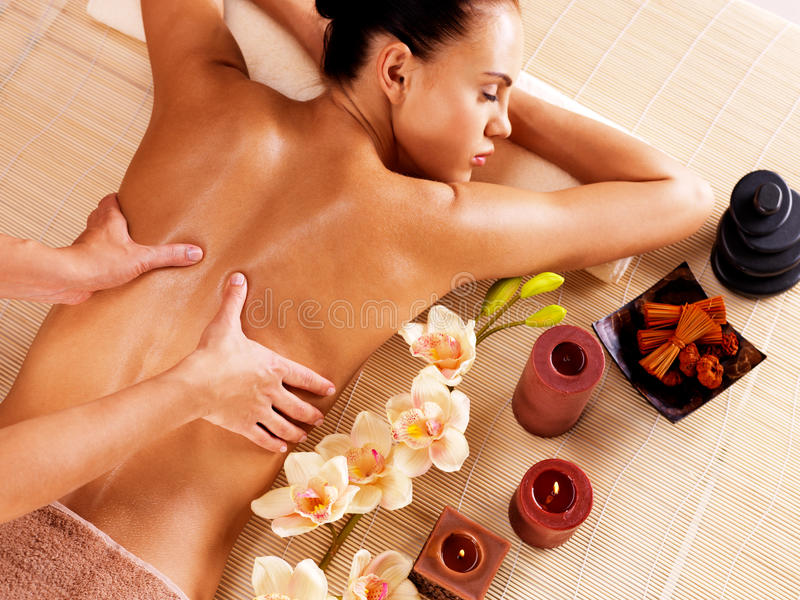 Massagista que faz a massagem na parte traseira da mulher no salão de beleza dos termas foto de stock