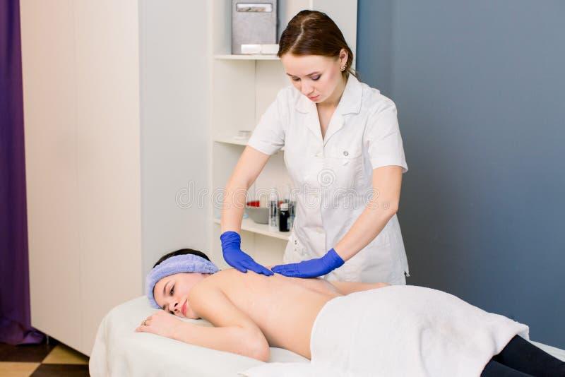 Massagista que faz a massagem na parte traseira da mulher no sal?o de beleza dos termas Massagem em um centro da beleza fotografia de stock royalty free
