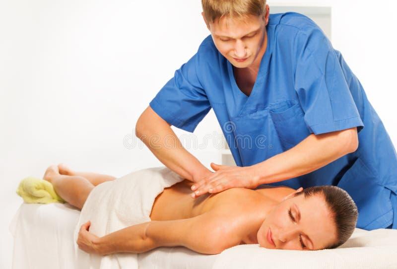Massagista que faz a massagem no corpo da mulher no salão de beleza dos termas fotografia de stock royalty free
