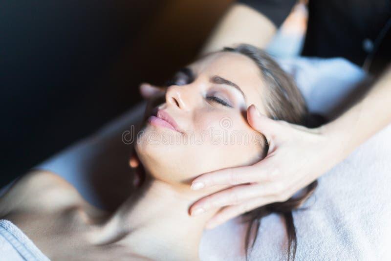 Massagista que faz massagens a cara de um bonito, jovem mulher que encontra-se no imagens de stock royalty free