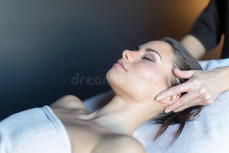 Massagista que faz massagens a cara de um bonito, jovem mulher que encontra-se no fotografia de stock