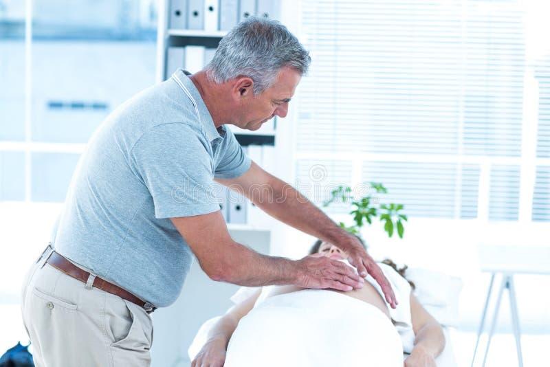 Massagista que faz massagens a mulher gravida imagem de stock royalty free