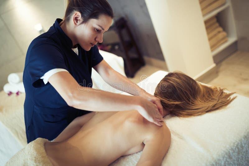 Massagista que faz massagens o cliente fêmea no recurso imagem de stock