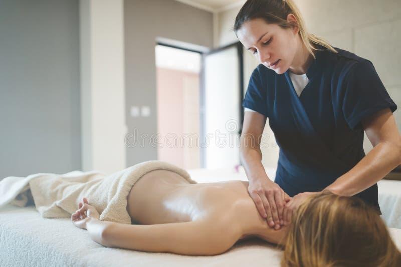 Massagista que faz massagens o pescoço e os sholders do cliente imagem de stock royalty free