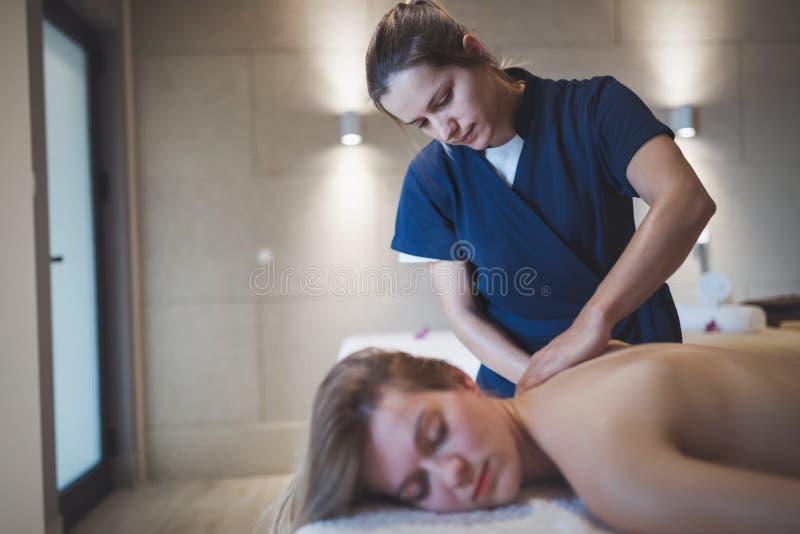 Massagista que faz massagens o pescoço e os sholders do cliente imagens de stock