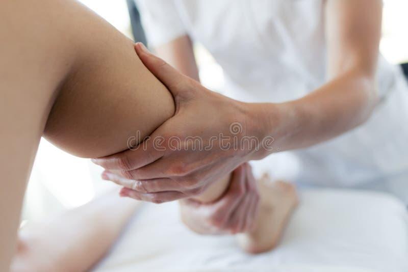 Massagista que faz massagens os pés da mulher gravida no centro dos termas fotografia de stock