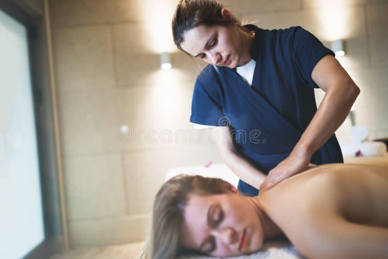 Massagista que faz massagens para trás da fêmea fotos de stock