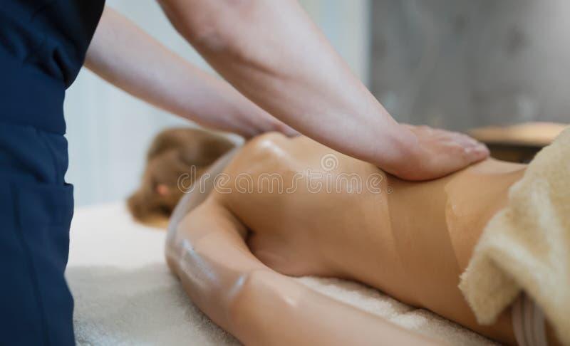 Massagista que faz massagens para trás da fêmea imagens de stock royalty free