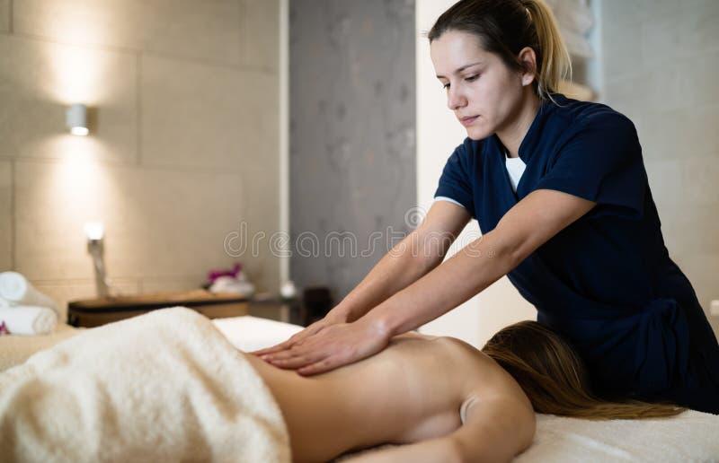 Massagista que faz massagens para trás da fêmea fotografia de stock